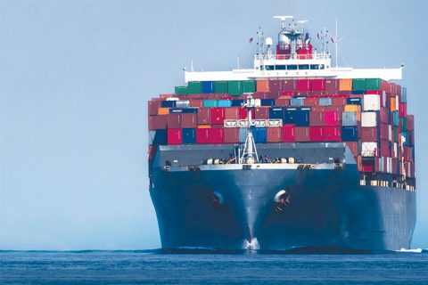 Image of a boat on the ocean with containers stored on the front of the ship.