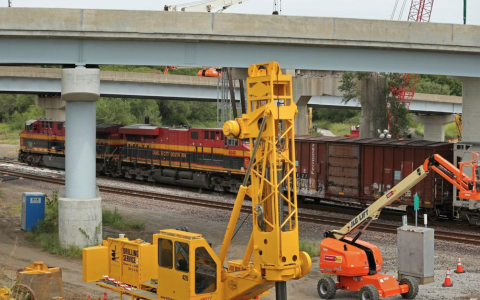 A Kansas City Southern freight train moves across tracks beneath feeder ramps to the Martin Luther King Bridge and past construction equipment on Thursday, Aug. 29, 2019, in East St. Louis. The Illinois Department of Transportation announced the bridge will remain closed until next summer at the earliest because extra freight traffic pushed through the region has slowed their ability to work at pace. Photo by Christian Gooden, cgooden@post-dispatch.com
