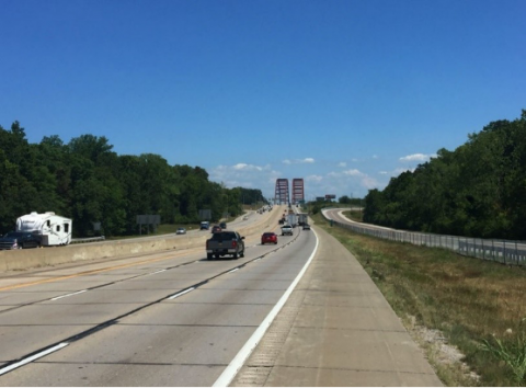 Photo showing a highway with cars and trucks driving on it